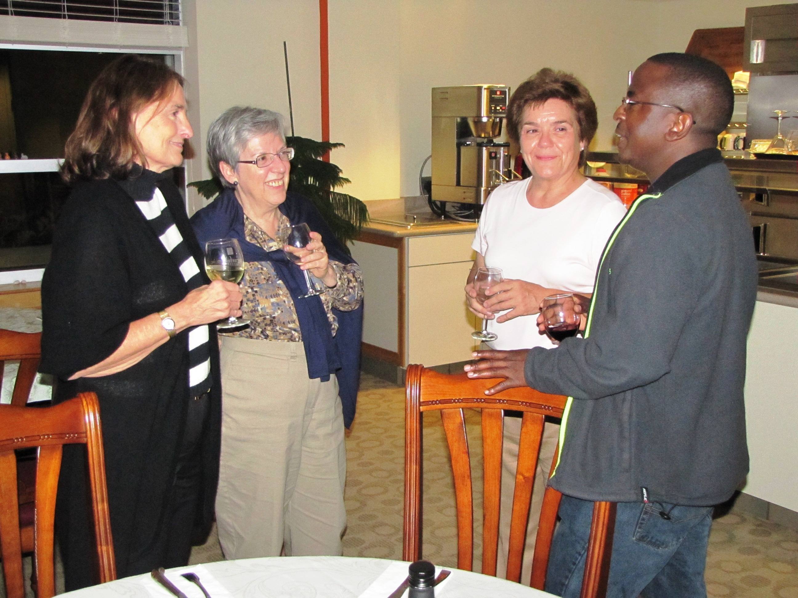 L-R Linda Scott, Graciela Etchart, and Diane Conoccholi listen to Fr. Barnabas Simatende, OMI at the Saturday night social